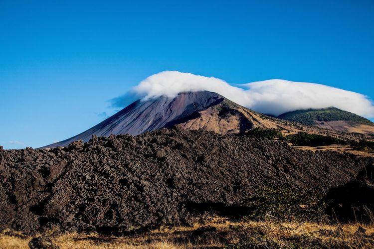 Cloud on mountain against blue sky