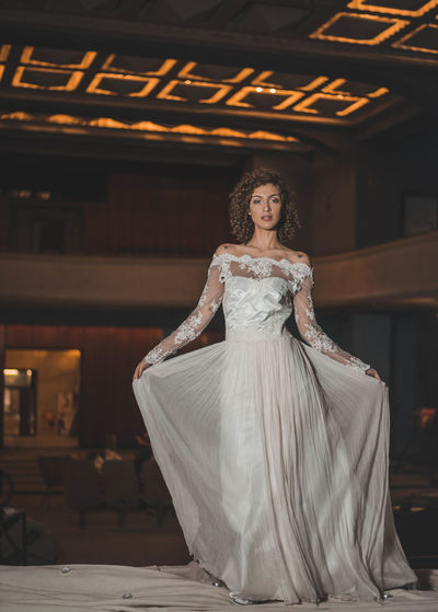 Portrait Of Beautiful Woman Holding Wedding Dress While Standing In Old Building