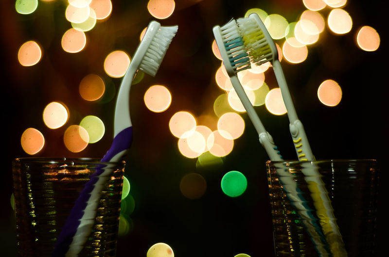 Close-up of toothbrush against illuminated lights