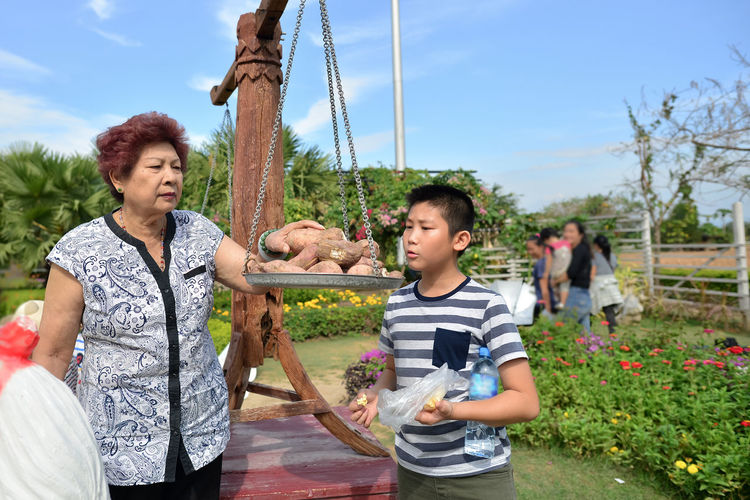 Grandmother and grandson keeping sweet potato on weight scale