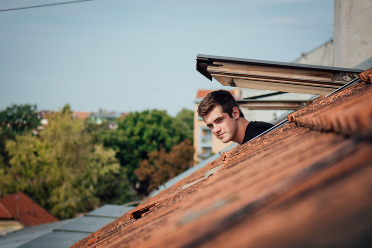 Low angle view of man standing on roof against sky