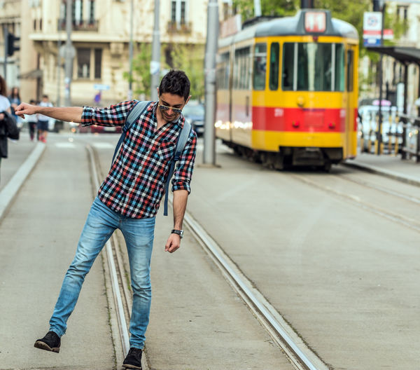 Railsway Transportation Mode Of Transportation One Person Casual Clothing Young Adult Public Transportation Real People Lifestyles Full Length Rail Transportation Young Men Track Leisure Activity Railroad Track City Architecture Land Vehicle Focus On Foreground Men Outdoors