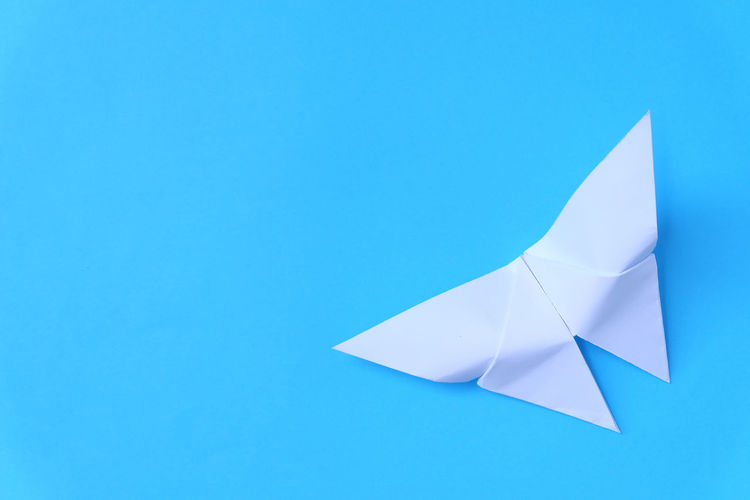 High angle view of paper boat over blue background