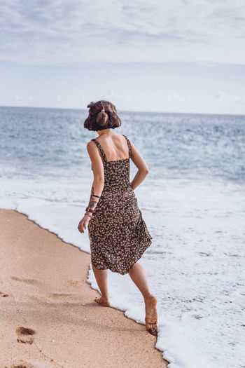 Rear view of woman standing on beach against sea
