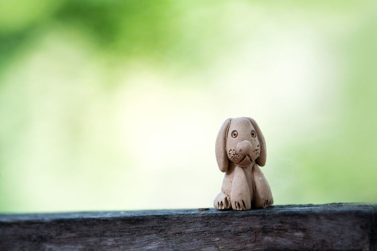 Clay doll dog on wood.