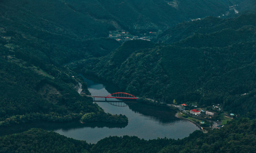 Aerial view of river amidst green mountains