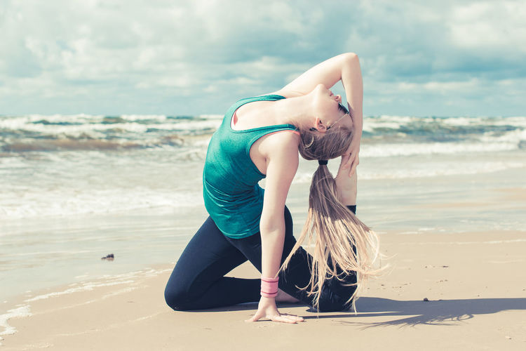 Side View Of Young Woman Doing Yoga At Beach Against Cloudy Sky