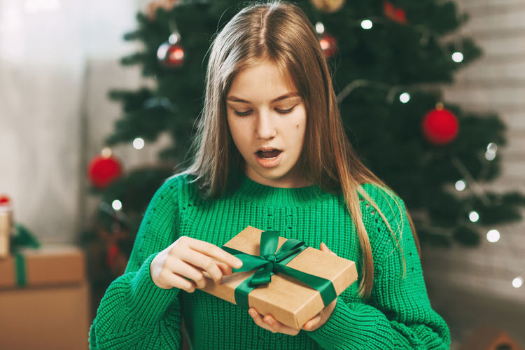 A beautiful girl with a surprised face opens a kraft paper gift