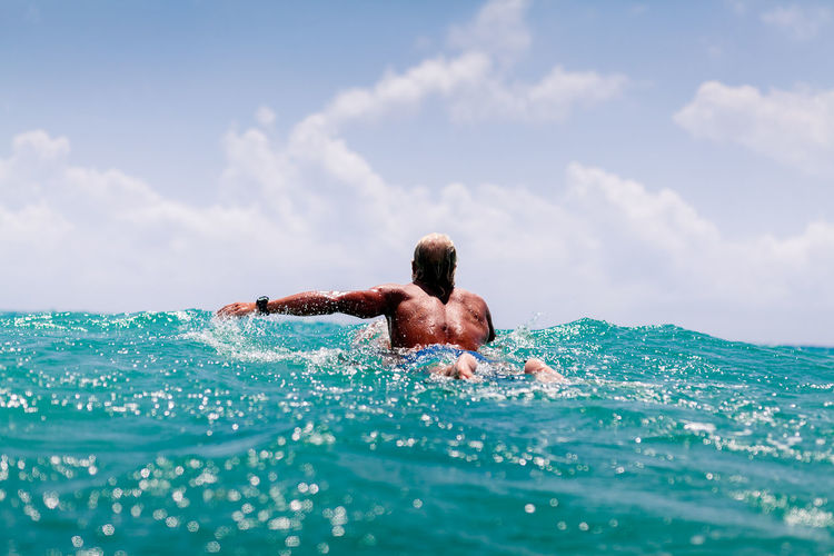 Man swimming in sea against sky