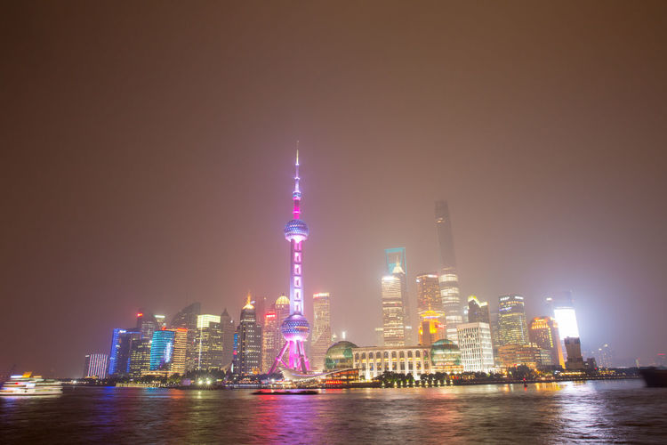 Oriental Pearl Tower By Huangpu River In City At Night