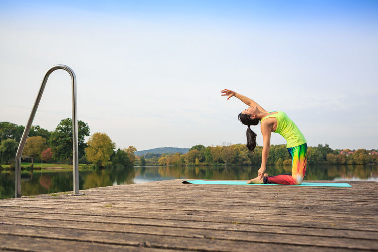 Side view of woman exercising on pier over river against sky