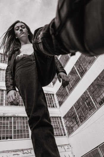 Low Angle Portrait Of Young Woman Walking Against Building In City