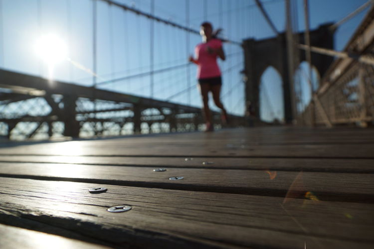 Full length of man standing on footbridge against clear sky