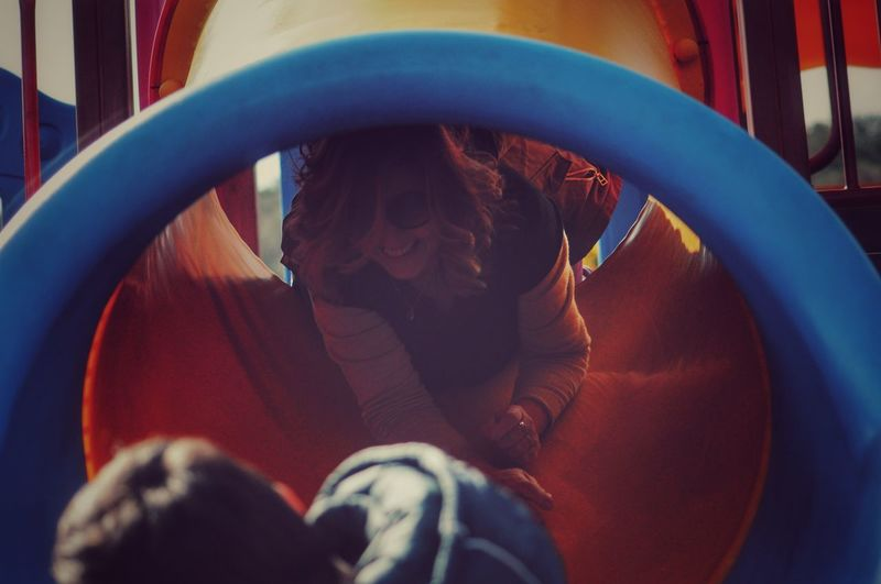 Low Angle View Of Woman Sliding In Slide At Playground