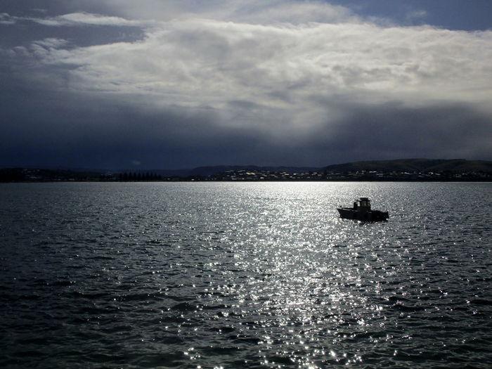 Silhouette sailboat sailing on sea against sky