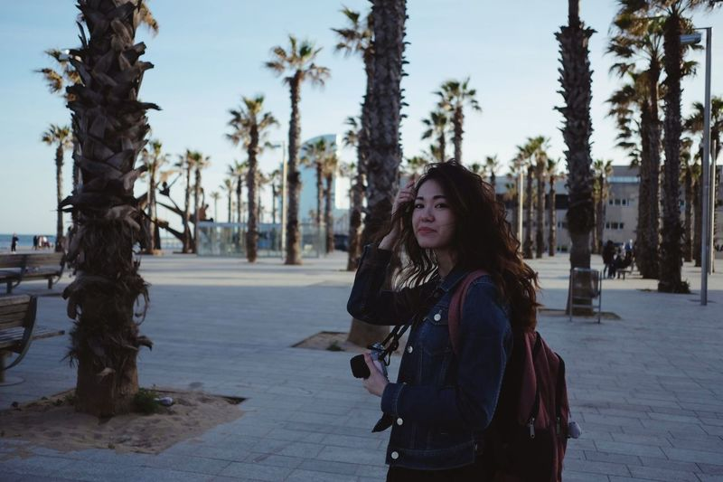 Portrait of young woman standing by palm trees