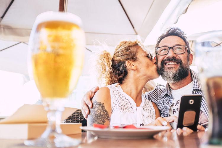 Woman kissing man while having food at table