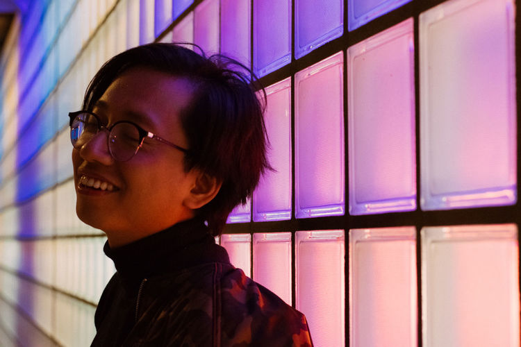 Illumination Close-up Contemplation Eyeglasses  Gay Glasses Hairstyle Headshot Human Face Indoors  Leisure Activity Lifestyles Looking Looking Away Mood Neon Nightlife One Man Only One Person Portrait Profile View Purple Real People Side View Smiling Young Adult