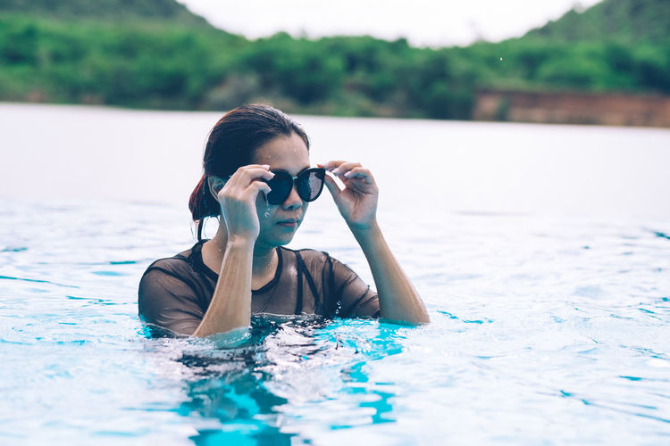 Mid Adult Woman Wearing Sunglasses In Sea