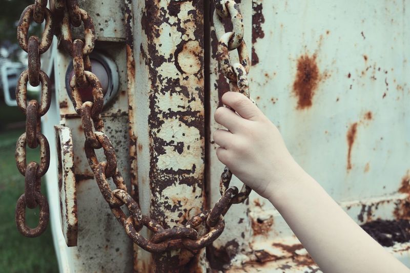 Close-Up Of Human Hand Holding Chain On Dumpster