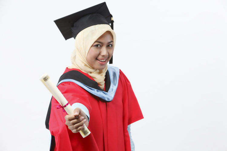 malay woman wearing red graduation gown with toothy smile Achievement Asian  Celebration Graduation Happy People Isolated Woman Beautiful Woman Cap Ceremony Certificate Cut Out Education Graduation Gown Holding Malay Ethnicity Mortarboard One Person Portrait Studio Shot Success Toothy Smile University Student White Background Young Adult