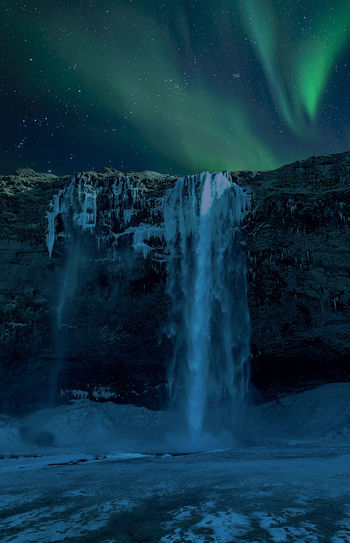 Scenic view of waterfall against aurora borealis in sky during winter