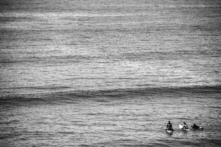 High angle view of surfers surfing in sea