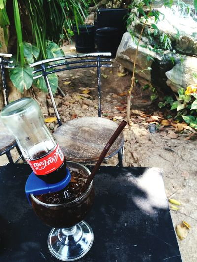 Nakhon Pathom, Thailand - Marh 2, 2018: Bottle of coke or cola in glass of water with ice on the black table at hangar café, Nakhon Pathom, Thailand. Freshness drink concept. Chair Coke Container Cool Freshness Hungry Logo Refreshment Soda Thirsty  Black Bottle Cafe Cocacola Cold Design Desıgn Drink Fresh Full Frame Resturant Soft Drink Straw Table