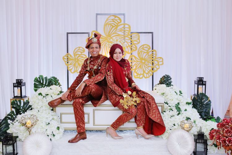 Portrait of smiling newlywed couple sitting at wedding ceremony