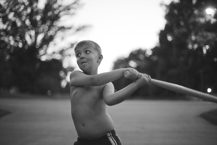 A seven-year-old boy swings a plastic bat during a mid-summer evening. Action Baseball Bat Black And White Boys Childhood Day Elementary Age Focus On Foreground Leisure Activity Lifestyles MidWest One Boy Only One Person Outdoors People Playing Real People Rural Shirtless Standing Summer Swing Tree Whiffle Ball Sommergefühle