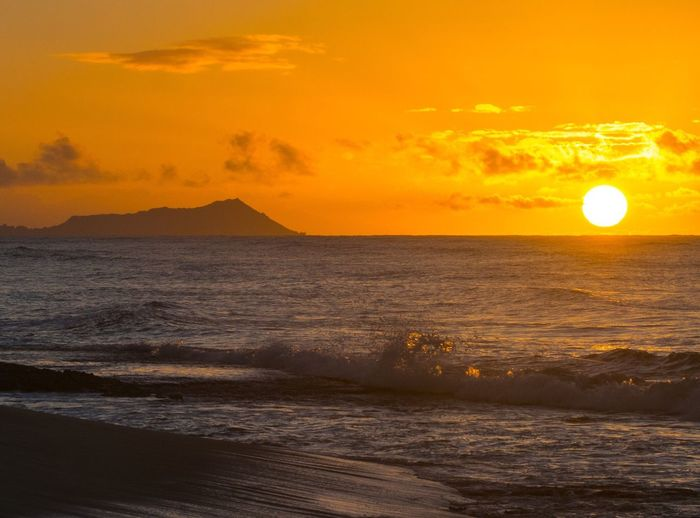 Scenic view of beach and sea against orange sky during sunset