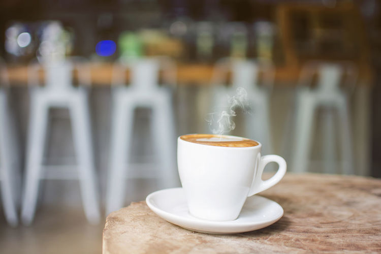 White cup of hot steaming coffee on an old log in the cafe with blurred coffee bar background Caffeine Chair Steam Aroma Bar Cafe Coffee Coffee - Drink Cup Drink Hot Drink Latte Log Mug No People Refreshment Roasted Table White White Color
