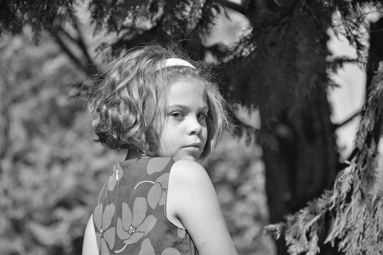 Rear View Portrait Of Girl Against Tree On Sunny Day