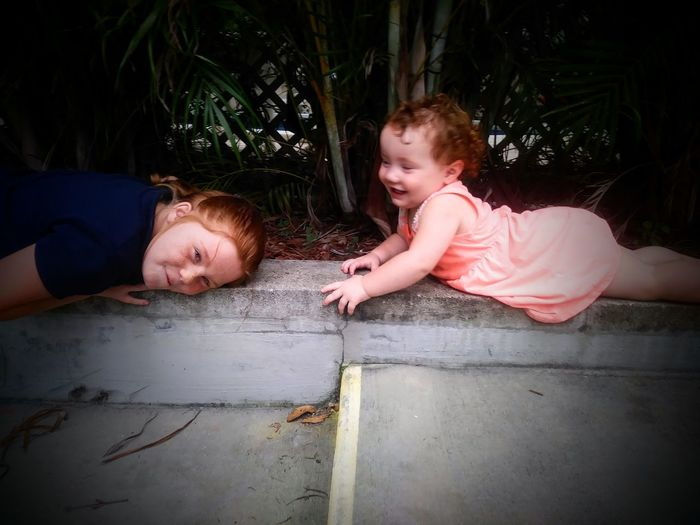 High angle view of playful sisters lying by plants at park
