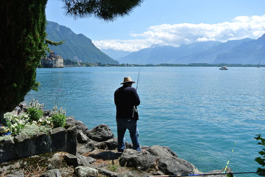 Connected By Travel Lost In The Landscape Man With Hat Water Fishing Hat View From The Back Landscape Beauty In Nature Nature Mountains Lake View Nofilter Switzerland Perspectives On Nature Summer Exploratorium