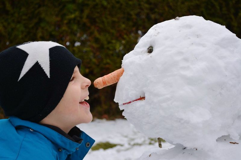 Side View Of Cheerful Boy Standing By Snowman