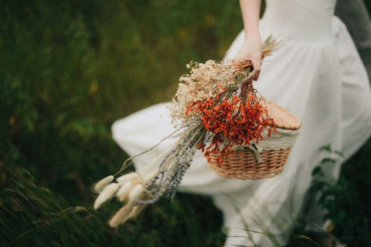 Close-up of bride holding flowering plants with basket