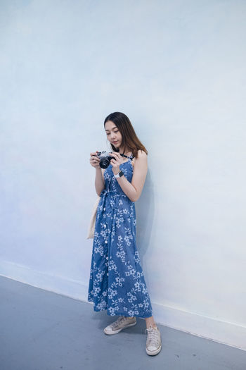 Full length of woman holding camera standing against wall