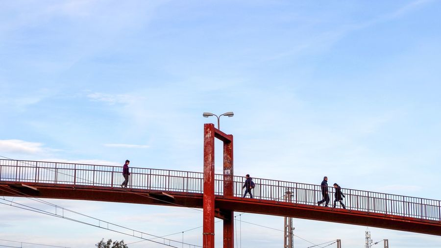 People standing on footbridge against sky