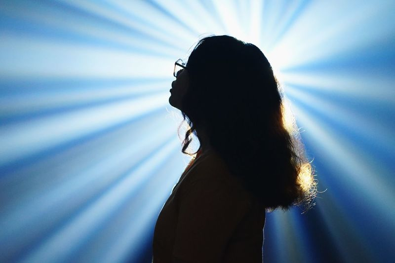 Side View Of Woman Standing Against Light Beams