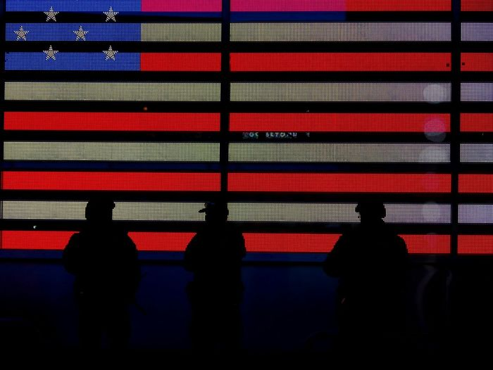 Silhouette Police Force Standing Against American Flag At Times Square