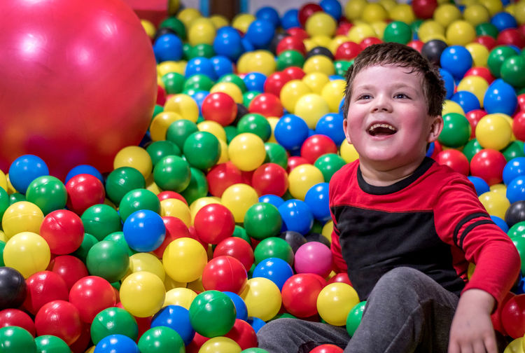 Portrait of smiling boy with multi colored balloons