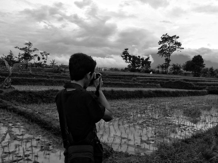 Male Photographer Photographing Through Camera While Standing On Field