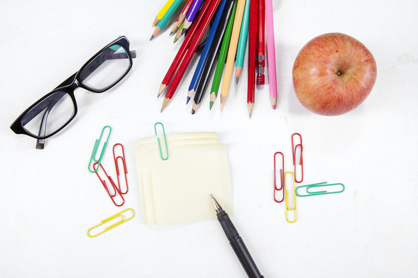 Apple Coloring Pencils Glasses Indoors  Large Group Of Objects Multi Colored No People Paper Clips Pen Rubber Band Stationary Still Life Table Variation