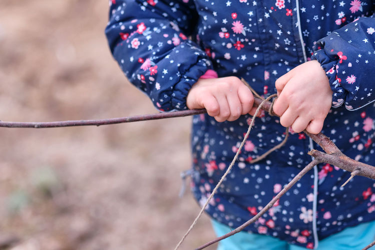 Midsection of girl tying rope to stick while standing outdoors