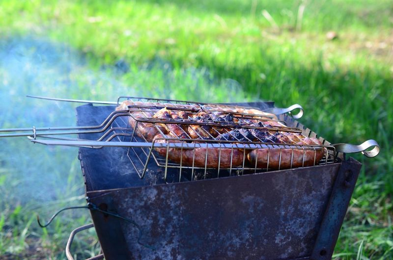 Abandoned cooking on barbecue grill in field