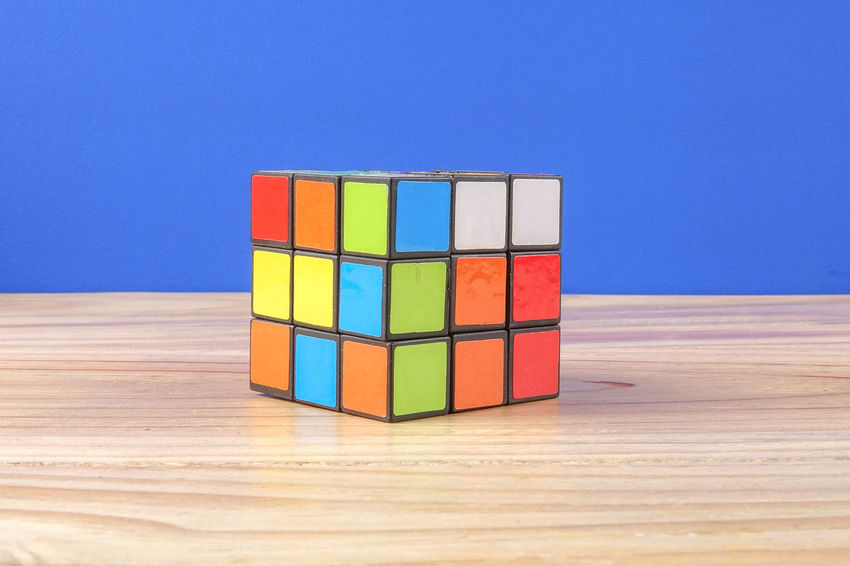 RUBIK'S CUBE , CREATIVITY TOY Creativity Rubik Cube Balance Block Blue Clear Sky Copy Space Cube Shape Day Design Geometric Shape Indoors  Intelligence Multi Colored No People Rubik Shape Sky Stack Still Life Table Toy Toy Block Wood - Material