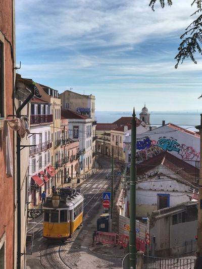 Lisbon historic alfama district. Alfama Historic Street Scene Streetcar Tram Building Exterior Architecture Built Structure Sky City Nature Mode Of Transportation Transportation Building Residential District Outdoors Street High Angle View No People Land Vehicle Water