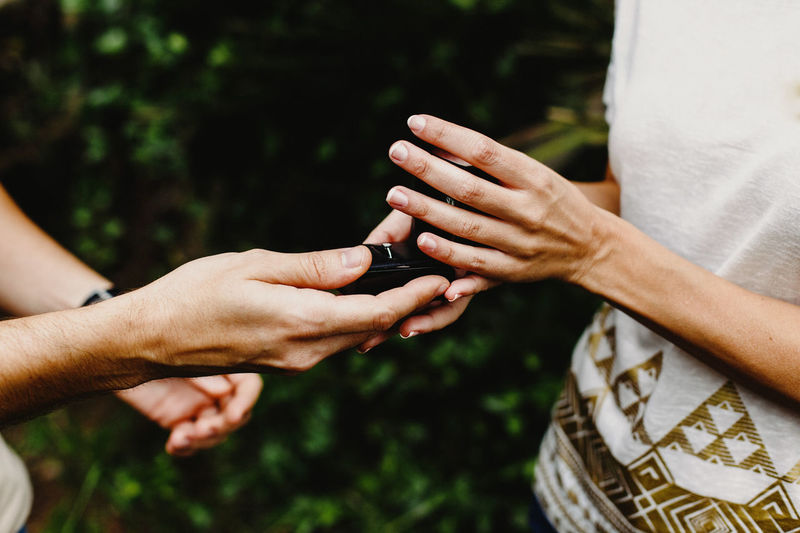 Cropped image of man giving ring to woman