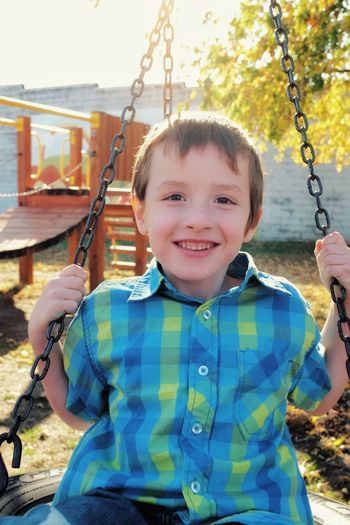 Portrait of smiling boy sitting on swing